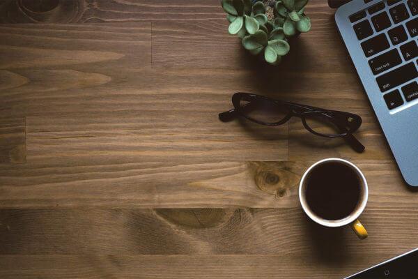 Schreibtisch mit Tasse, Brille und Laptop